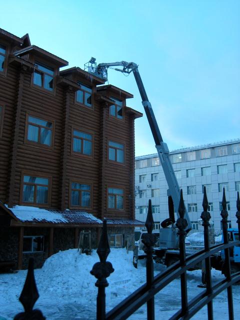 In de avondschemering wordt er nog gewerkt om de sneeuw van het Belka Hotel te verwijderen