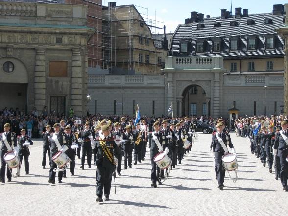 De ceremoniële wisseling van de wacht wordt begeleid door een orkest. Op de achtergrond zijn de drommen mensen te zien die zich voor dit optreden hebben verzameld.