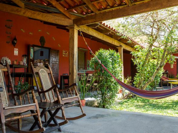 Onder de veranda van Casa Aroma de Campo staan gezellige zitjes, zoals schommelstoelen.