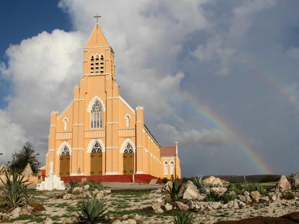 Ansichtkaartmateriaal: de kerk van Sint Willibrordus op Curacao met niet één, maar twee regenbogen