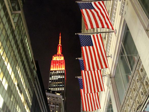Het Empire State Building is 's nachts prachtig verlicht, telkens in een andere kleur. Op de voorgrond zie je een rij Amerikaanse vlaggen, iets wat je vaak ziet in New York