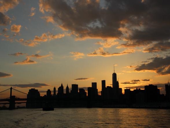 De skyline van Manhattan met op de achtergrond de ondergaande zon. Diverse rederijen bieden riviercruises bij zonsondergang aan