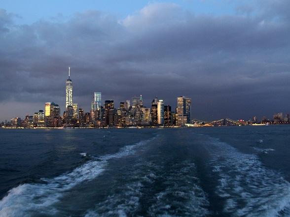 In het donker fonkelt de skyline van New York je met honderden lichtjes tegemoet