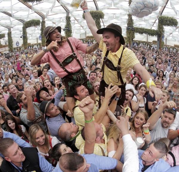 Feestgangers vieren de opening. Dit beeld is gemaakt met een fish-eye lens. Foto AP - Matthias Schrader