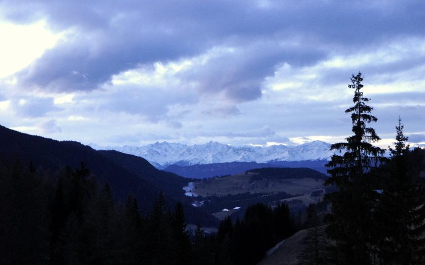 Van op de berg kan je in de verte de Alpen zien liggen.