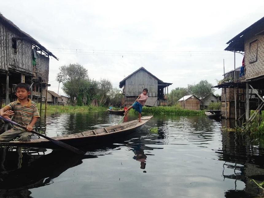 Kinderen op bootjes, huizen op palen