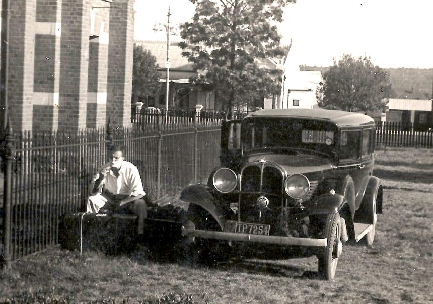 """Arie Pilon is zich aan het scheren naast de tot """"camper"""" omgebouwde Willy's Overland (1931) bij het huis van Paul Kruger"""