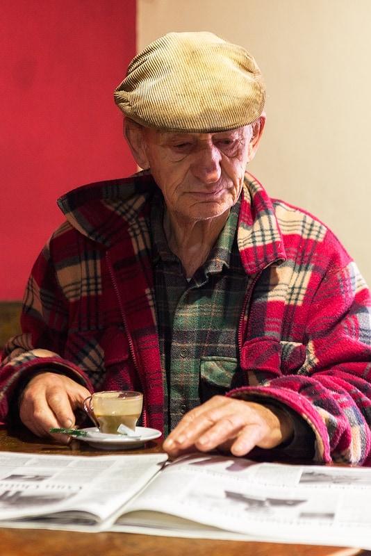 Oud mannetje met krant, Cafe in Santa Porto Moniz, Madeira, Portugal