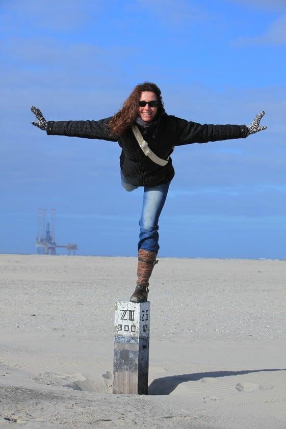 Sybylle Kroon in balans op strandpaal op het meest oostelijke puntje van Ameland. Links is een productieplatform in de Noordzee te zien.