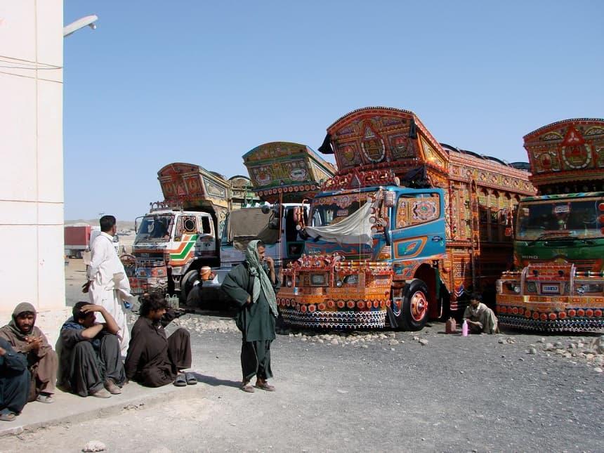 Kleurrijke opgepoetste kingsize vrachtauto's stralen op de parkeerplaats van de Iraans-Pakistaanse grens