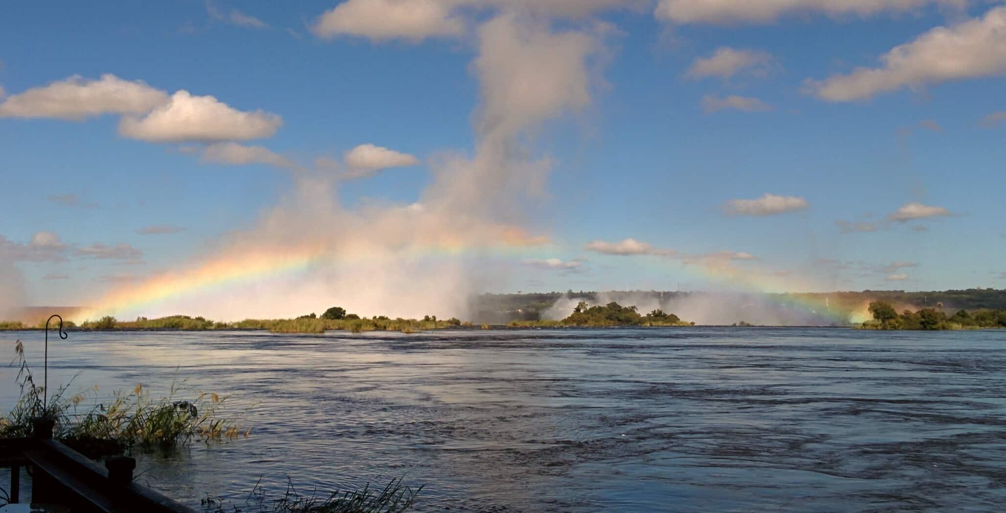De Victoria Falls onder een regenboog door de eeuwige sproeiregen van de waterval.