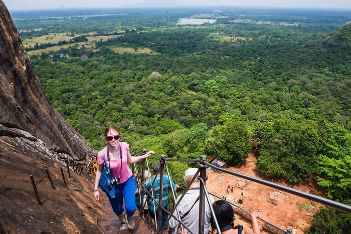 This is a photo of a female tourist climbing Sigiriya Rock Fortress, aka Lion Rock, a UNESCO World Heritage Site in Sri Lanka. Sigiriya Rock is easily the most popular thing to do in Sri Lanka.