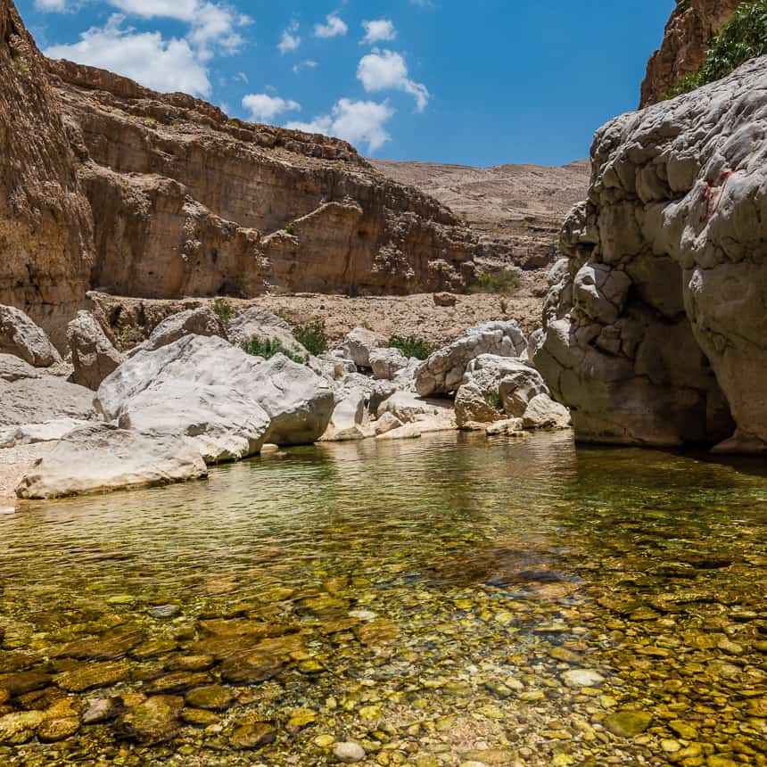 Rond geslepen stenen en lichtgroen water