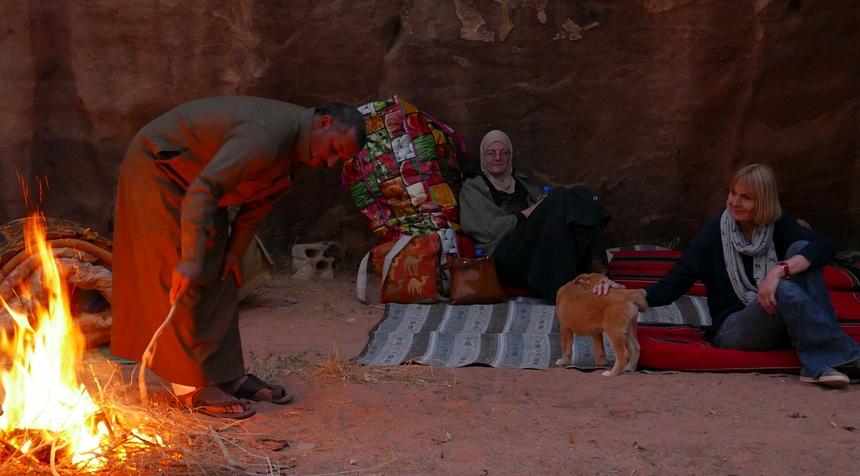 Kamelenman Mansour stookt het vuur op om eten te koken.