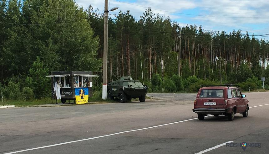excursie naar Chernobyl, net iets voor de slagboom staat een houten souvenirkraampje geflankeerd door een replica van een tank wat verdwaald langs de weg