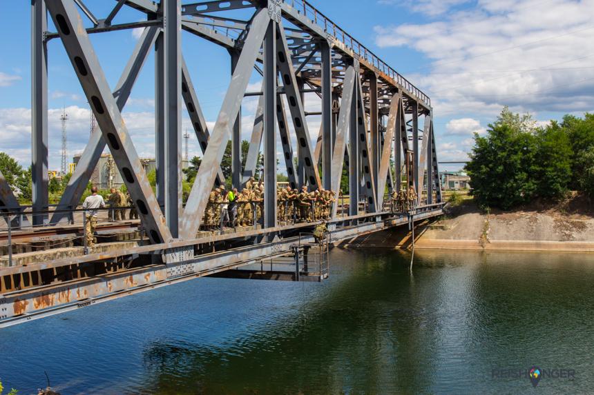 Even verderop hangen de soldaten camouflagepakken op de ijzeren spoorbrug die de rivier naast de centrale overstrekt
