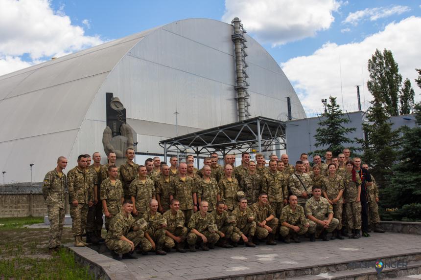 Een groep van zo'n 40 soldaten poseert breed lachend voor het monument