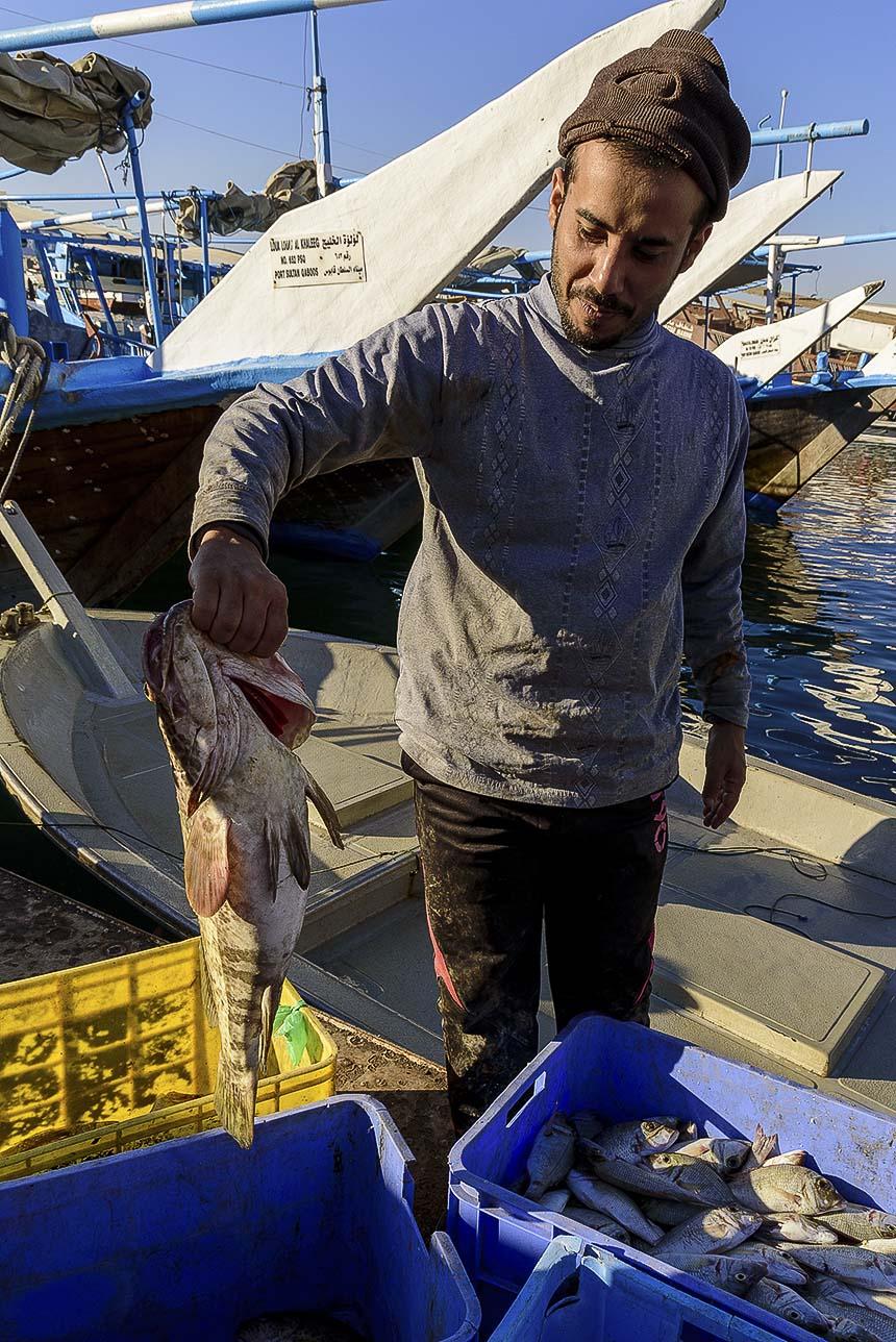 De vissers laten ons vol trots hun catch of the day zien