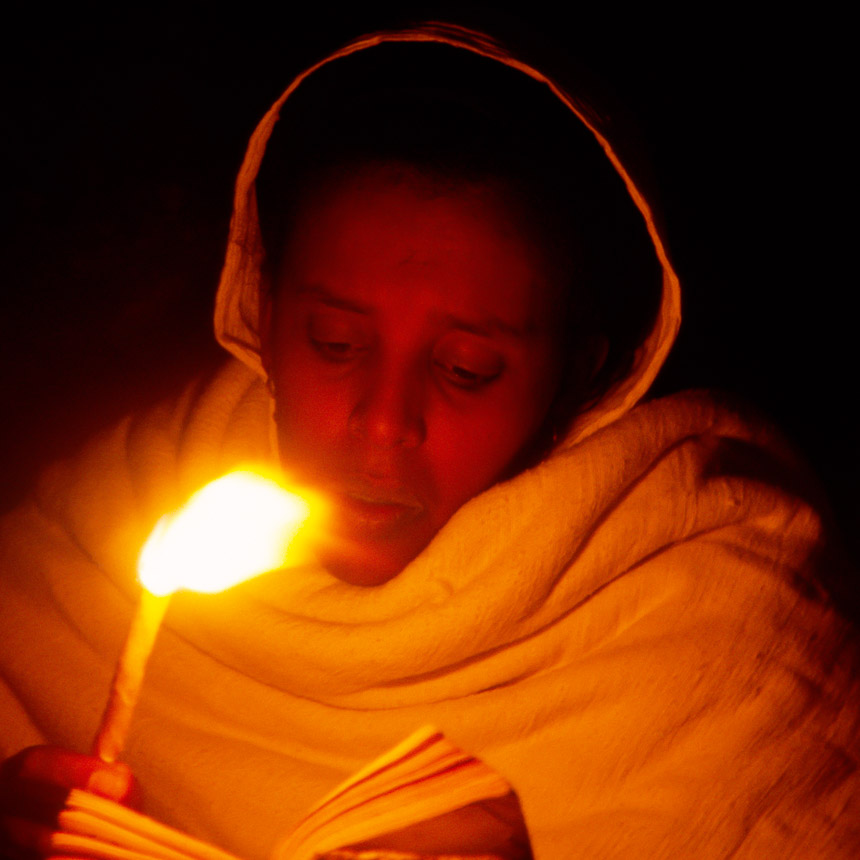 Jonge vrouw leest de bijbel bij kaarslicht in Ethiopië