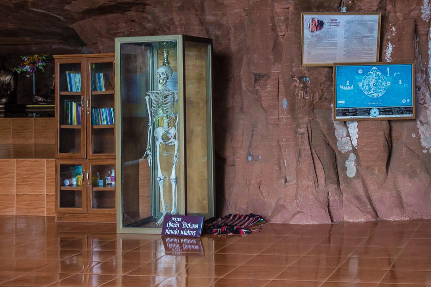Een hal in Wat Phu Tok met Boeddhabeelden en een skelet in een glazen kast