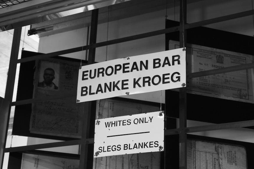 Entree Apartheidsmuseum met een selectie van de borden die eerder in kroegen en winkels hingen