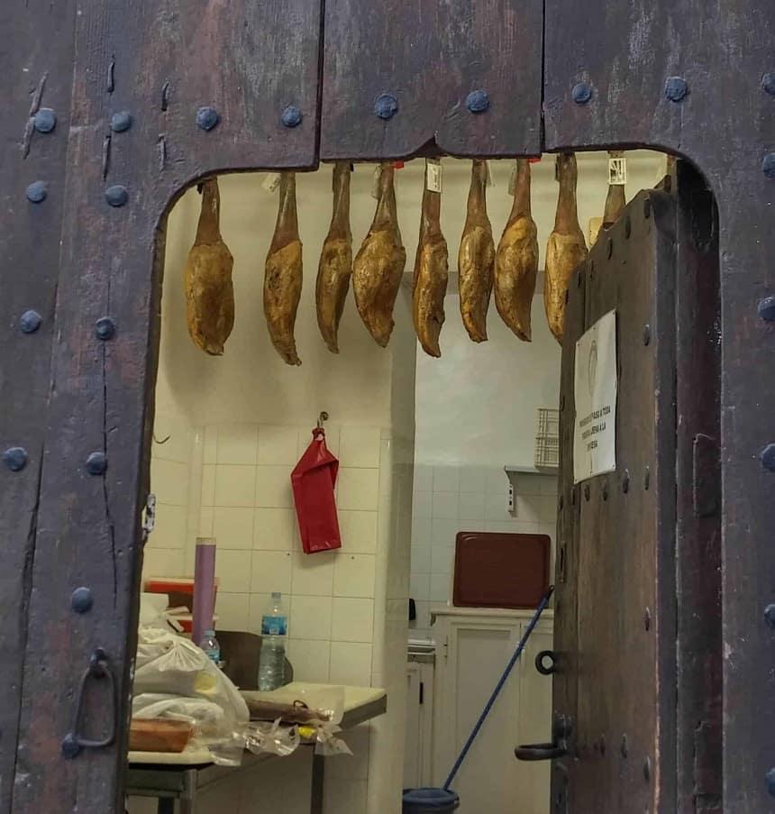 Hammen hangen te drogen bij de slager