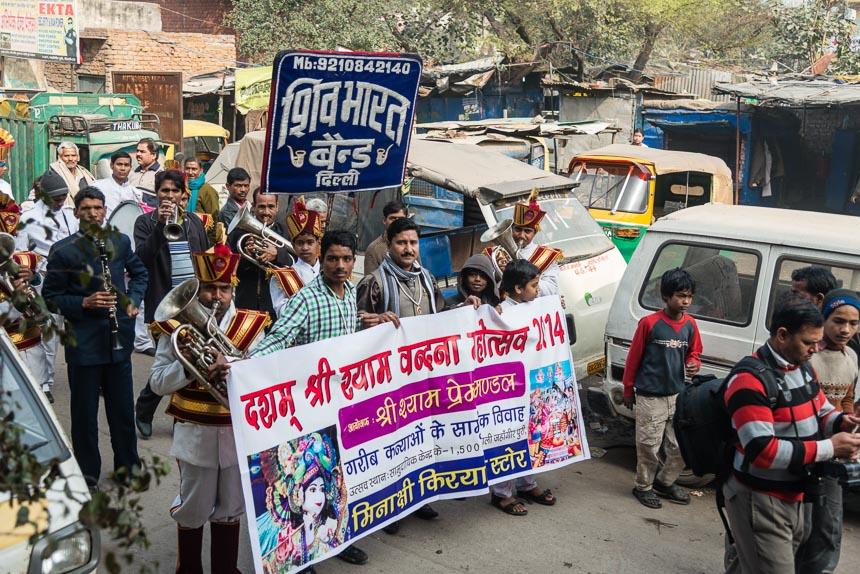 Jahangir Puri - Een drumband met een vaandel en een spandoek vult de straat met geluid en aanwezigheid,