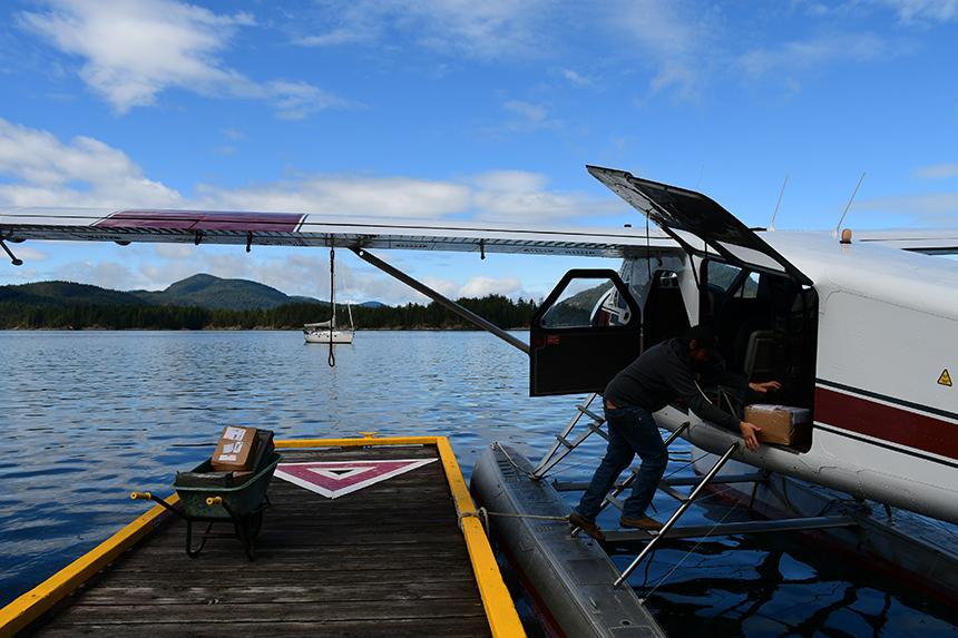 Post inladen in het Beaver postwatervliegtuig op de Campbell River - de post wordt er per watervliegtuig bezorgd