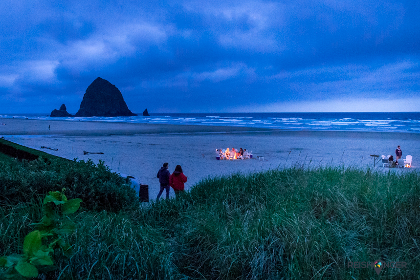 Verschillende kleine vuurtjes verlichten het strand van Cannon Beach