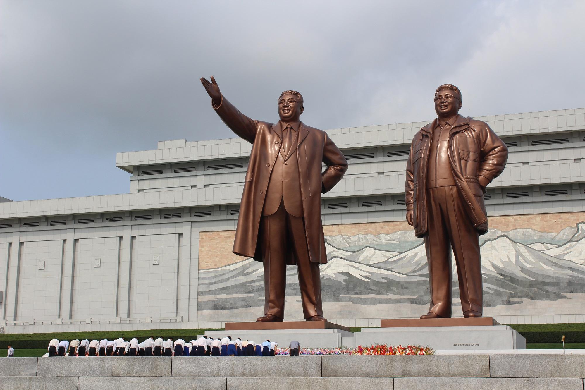 Buigen voor het standbeeld van Kim Jong Il En Kim Il Sung